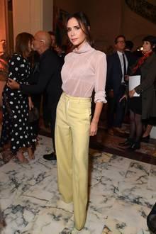 Während die Schuhe unter der zitronengelben Hose von Victoria Beckham komplett verschwinden, lässt sie oben herum etwas tiefer Blicken: Die leicht transparente Bluse lässt den wunderschönen Spitzen-BH der Modedesignerin hervorblitzen. Ein sexy Detail, das Victoria gekonnt einsetzt, um ihr Outfit Cocktail-Party-tauglich zu machen.