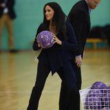 """Bei der Verleihung der """"Coach Core Awards"""" wird Herzogin Meghan selber aktiv und greift kurzerhandzum Ball. So richtig mitspielen kann sie auf ihren Heels von Aquazzura jedoch nicht. Und auch ihre Wickelbluse von Oscar de la Renta (ca. 1.900 Euro) ist nicht gerade die beste Sportswear."""