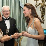 In einem schulterfreien, bodenlangen Kleid von Amada Wakeley zeigt sich Herzogin Catherine von ihrer gewohnt eleganten Seite. Silber verzierte Träger, viel Schmuck und Jimmy-Choo-Heels runden den funkelnden Look ab.
