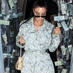 Wieso sollte man Geld für Kleidung ausgeben, wenn man die Banknoten aucheinfach in Form eines Mantels tragen kann? Kim Kardashian beweist mit diesem Outfit auf jeden Fall mal wieder ihre Vorliebe für ausgefallene Looks. Hier handelt es sich natürlich nicht um echte Geldscheine, sondern eine Vintage-Kreation von Designer Jeremy Scott, kombiniert mit Dollar-Overknees von Balenciaga.
