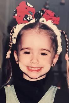 Lily Collins  Diesen zuckersüßen Schnappschuss aus Kindertagen teilt die Schauspielerin Lily Collins auf ihrem Instagram-Account. Zu sehen die kleine Lily mit einer großen Schleife im Haar.