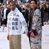 Durch den Sand bis zu ihren Plätzen stapfen auch Pharrell Williams und seine FrauHelen Lasichanh.