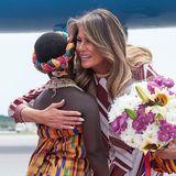 Liebevoll begrüßt die First-Lady eines der Kinder, welches ihr Blumen erreicht am Flughafen.