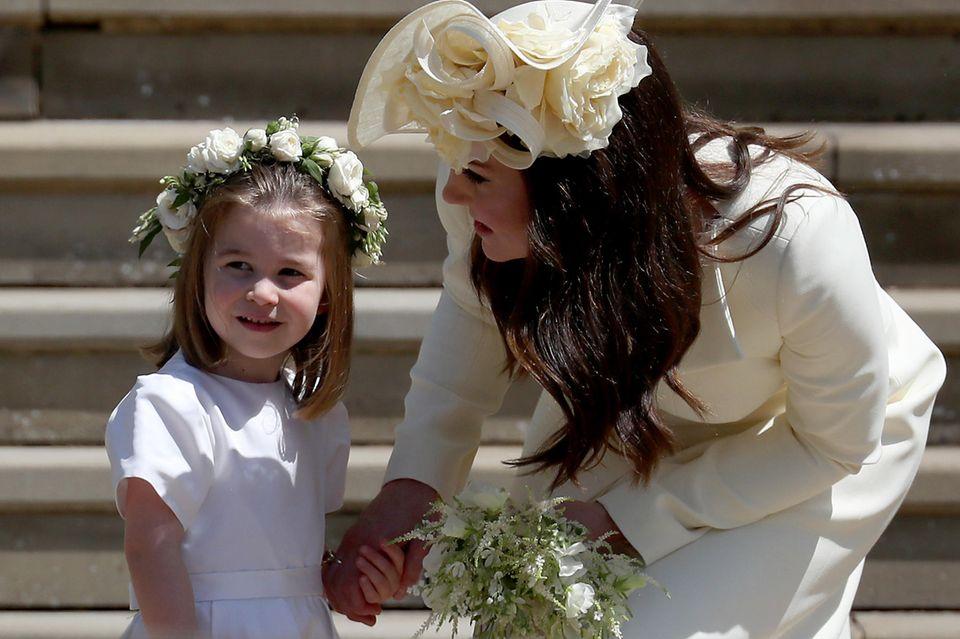 Herzogin Catherine flüstert Tochter Prinzessin Charlotte etwas bei der Hochzeit von Prinz Harry und Herzogin Meghan zu.
