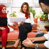 """Beim Treffen der """"Leaders of Tomorrow"""" in Jordanien erscheintKönigin Rania in einem durchweg klassisch-seriösenOutfit. In schwarzer Chino-Hose, weißer Bluseund farblich aufeinander abgestimmten Accessoireserinnert ihr Lookein wenig an den einer Stewardess. Insbesondere ihr dunkelrotes Halstuch..."""
