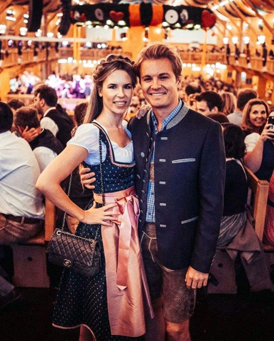 """""""Er sieht heiß aus in Lederhosen"""" schreibt Vivian Rosberg zu diesem Pärchen-Posting auf Instagram. Gemeinsam mit ihrem Mann Nico Rosberg besucht sie das Oktoberfest. Doch auch die hübsche Blondine sieht zauberhaft aus in ihrem feschen Wiesn-Look. Vivian Rosberg trägt ein ein blaues Dirndl mit rosafarbener Schürze und Details von Amsel Fashion. Dazu kombiniert sie die """"Classic"""" von Chanel."""