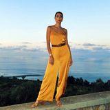 Zu einem eleganten, gelb-orangenen Overall kombiniert Rebecca einen klassischen Gucci-Gürtel. Ihr Haar trägt sie elegant zurückgesteckt.