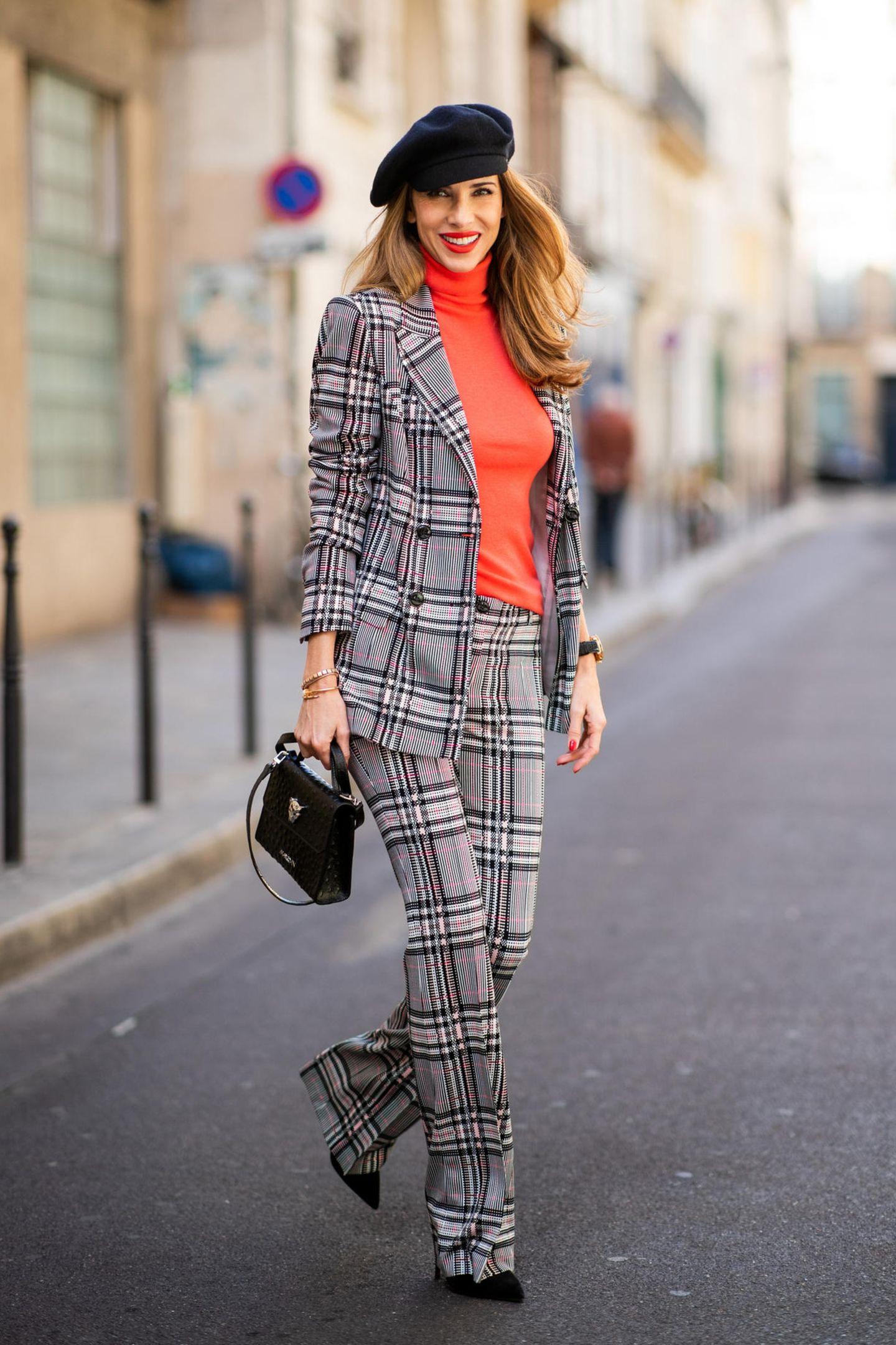 Bloggerin Alexandra Lapp passt sich zur Fashion Week in Paris natürlich auch Outfit-technisch der Stadt an. In einem karierten Hosenanzug mit knalligem Rollkragen-Pullover und raffinierten Details schlendert sie durch die Mode-Metropole.