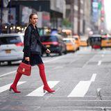 Was für heiße Overknees! Bloggerin Nina Suess legt kurzerhand den Straßenverkehr in New York lahm. Mit diesem Outfit kein Wunder. Zu einem dunklen Spitzenkleid und Lammfell-Lederjacke, kombiniert sie rote Overknee-Stiefel und eine Statement-Bag in derselben Farbe.