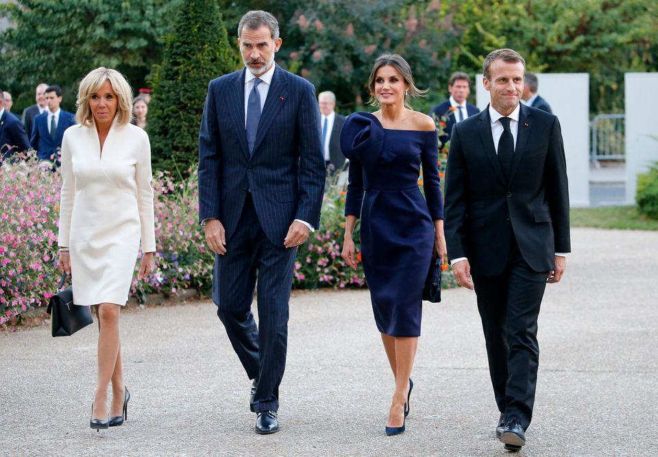 Letizia nämlich übertrifft Madame Macron in ihrem schulterfreien Etuikleid mit Blüten-Detail fast noch an Eleganz, nur das Dunkelblau ist im Vergleich zu Brigittes weißem Look doch eher zurückhaltend.