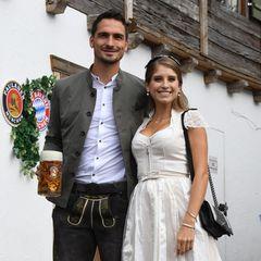Ganz im weißen Dirndl aus ihrer eigenen Kollektion bezaubert Cathy Hummels beim traditionellen Oktoberfest-Besuch der FC-Bayern-München-Mannschaft an der Seite ihren Mannes Mats Hummels. Dazu trägt sie silberne Schleifen-Pumps und eine passende Handtasche.