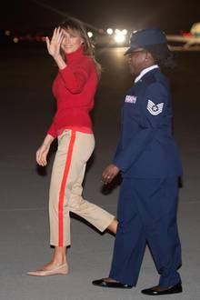 Lächelnd winkt Melania Trump den Fotografen als sie nach ihrer sechstägigen Afrikareise wieder in den USA landet. Für den Flug entschied sie sich für eine beige Hose mit rotem Streifen, einen roten Rollkragenpullover und helle Ballerinas.
