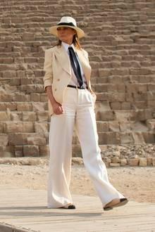 Sie trägt eine helle Marlenehose mit einer cremefarbenen Bluse und einem hellen Blazer von Ralph Lauren. Schwarze Details machen den Look spannend - die zweifarbigen Chanel-Ballerinas passen perfekt dazu.