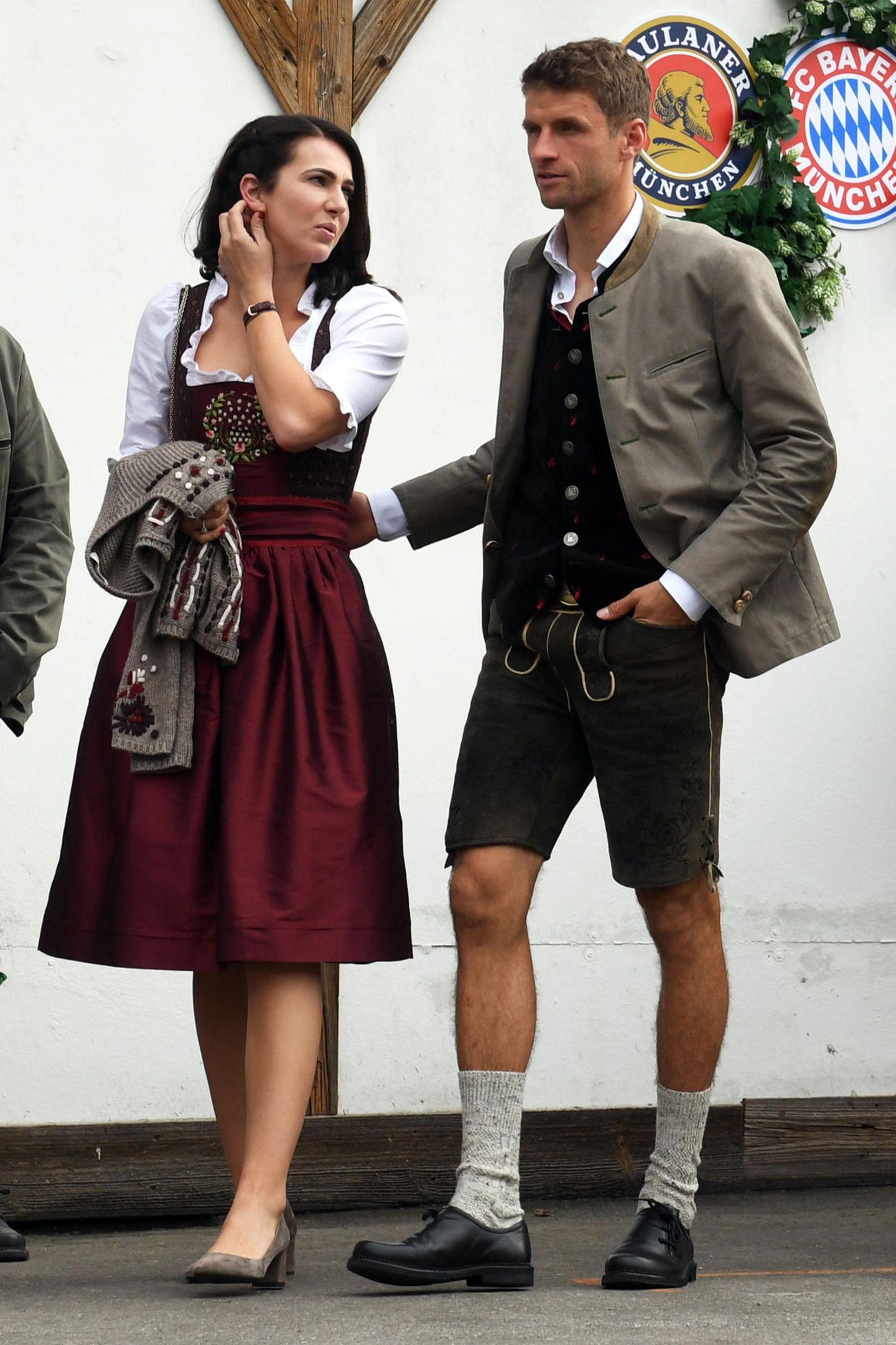 Lisa und Thomas Müller setzen auf klassische Tracht bei ihrem Besuch auf dem Oktoberfest. Die Spielerfrau trägt ein bordeauxfarbenes Dirndl mit schlichter Rüschen-Bluse und gestrickter Trachtenjacke, der Fußballer trägt zur dunklen Lederhose Weste und Janker.