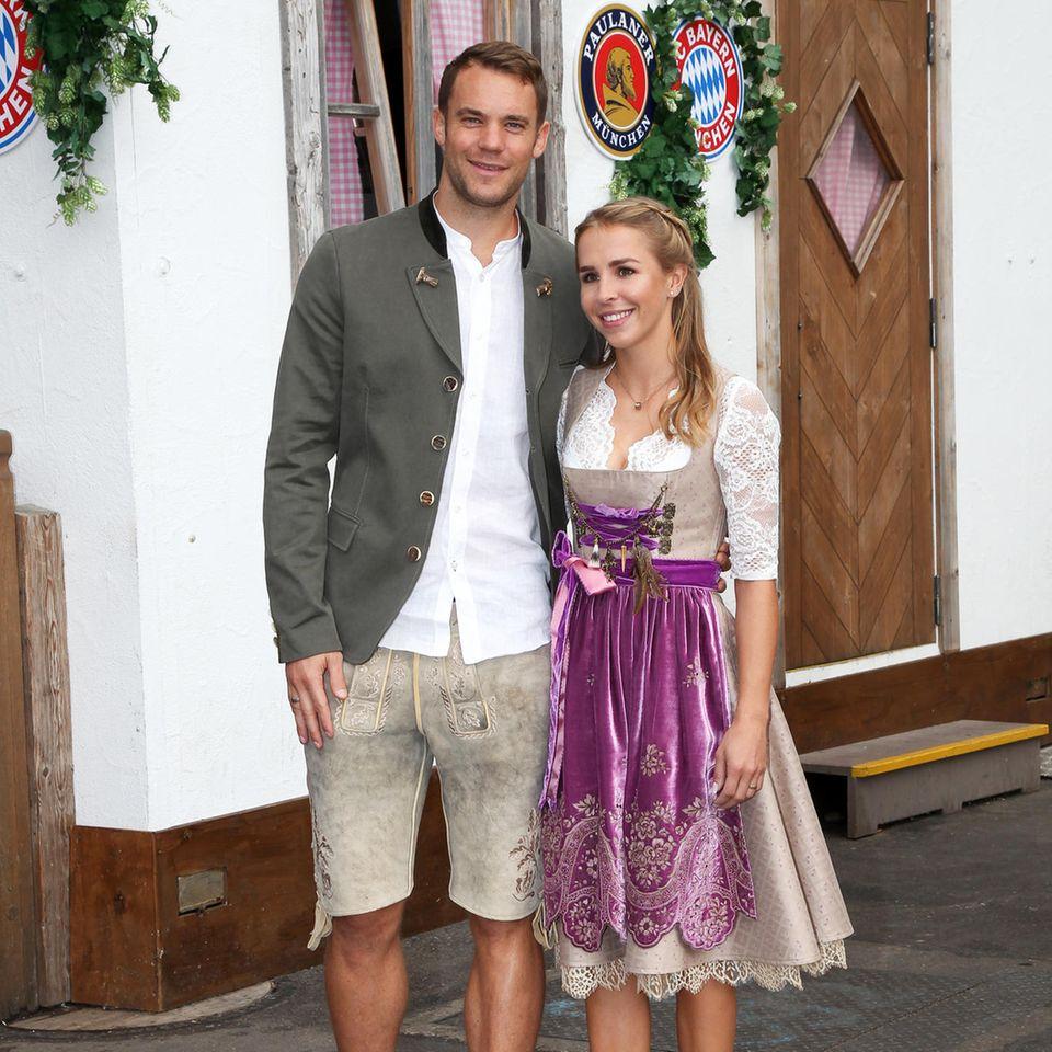 Auch Torwart Manuel Neuer und seine Frau Nina dürfen bei dem Besuch des FC Bayern Münchens auf der Wiesn nicht fehlen. Das Paar hat seine Looks farblich aufeinander abgestimmt. Lisa Neuer trägt ein beigefarbenes, edles Dirndl mit lilafarbener Samt-Schürze, Manuel trägt eine Lederhose in einem ähnlichen Beige-Ton.