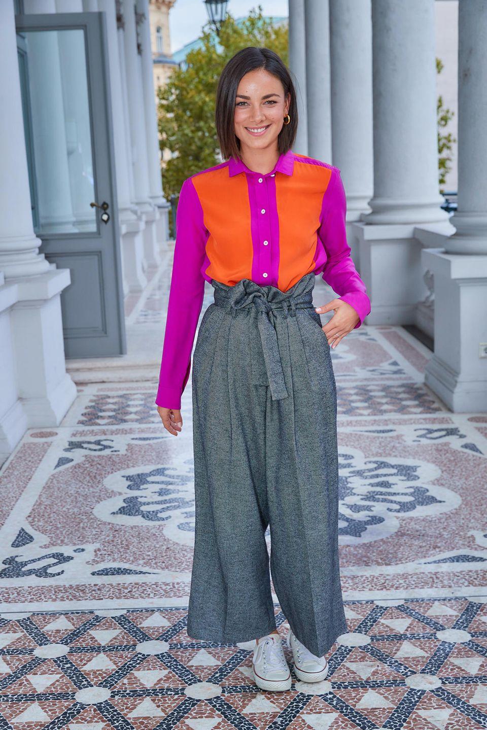 Dieser Look beweist, dass Janina Uhse Ahnung von Mode hat. Ihre leuchtende Bluse kombiniert die Schauspielerin mit einer grauen Culotte und weißen Sneakern. Auch wenn dieses Outfit für einige Betrachter auf den ersten Blick womöglich nicht ganz stimmig zu sein scheint, liegt Janina damit total im Trend.