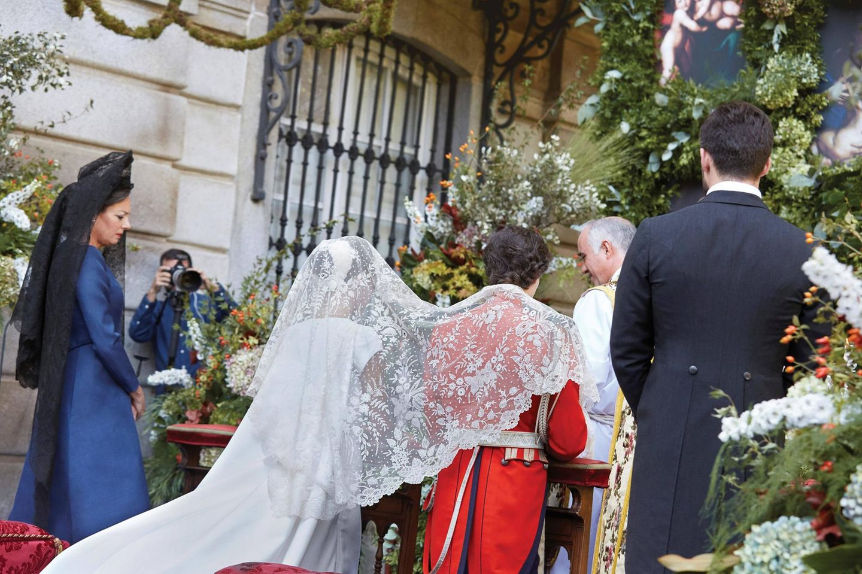Für die Zeremonie trägt sie einen Spitzenschleier, der ihre und die Schultern ihres Bräutigams verdeckt. Ihr dunkelbraunes Haar trägt sie zu einem edlen Chignon gesteckt.