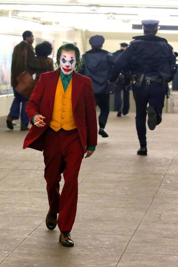 """Die neuesten Bilder vom """"Joker""""-Filmsetzeigen Schauspieler Joaquin Phoenix in einer New Yorker U-Bahn, in der er sich in seiner Rolle als Joker in aller Ruhe eine Zigarette anzündet, während Polizeikräfte an ihm vorbeirennen. Was er da wohl wieder verbrochen hat?"""