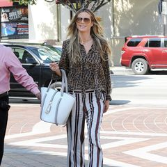 Da konnte sich wohl jemand nicht entscheiden: Multitalent Heidi Klum greift bei ihrem Outfit direkt zu zwei angesagten Mustern und kombiniert sie miteinander. LänglicheStreifen an der Hose und ein sexy Animal-Print auf ihrer Bluse und ihren Plateau-Stilettos würden bei uns darauf hinweisen, dass es beim Griff in den Kleiderschrank noch sehr dunkel gewesen sein musste - bei Heidi Klum sieht diese Kombinationjedoch einfach nur stylisch aus.