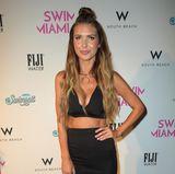 """Mit einem schwarzen Pencilskirt und einem BH-Oberteil erscheint Audrina auf der Swimmiami Modenshow im Jahr 2017, wo sie ihr eigenes Modelabel""""Prey Swim""""vorstellt."""