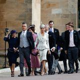 Robbie Williams und Ayda Field leiten eine Gruppe von Gästen an. Dabei sticht Ayda in ihrem weißen Ensemble von Armani Privé zwischen all den dunklen Anzügen besonders hervor.