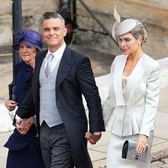 Robbie Williams kommt Hand in Hand mit seiner Frau Ayda Field und seiner Schwiegermutter Gwen. Tochter Teddy wird an diesem besonderen Tag Blumenmädchen sein.