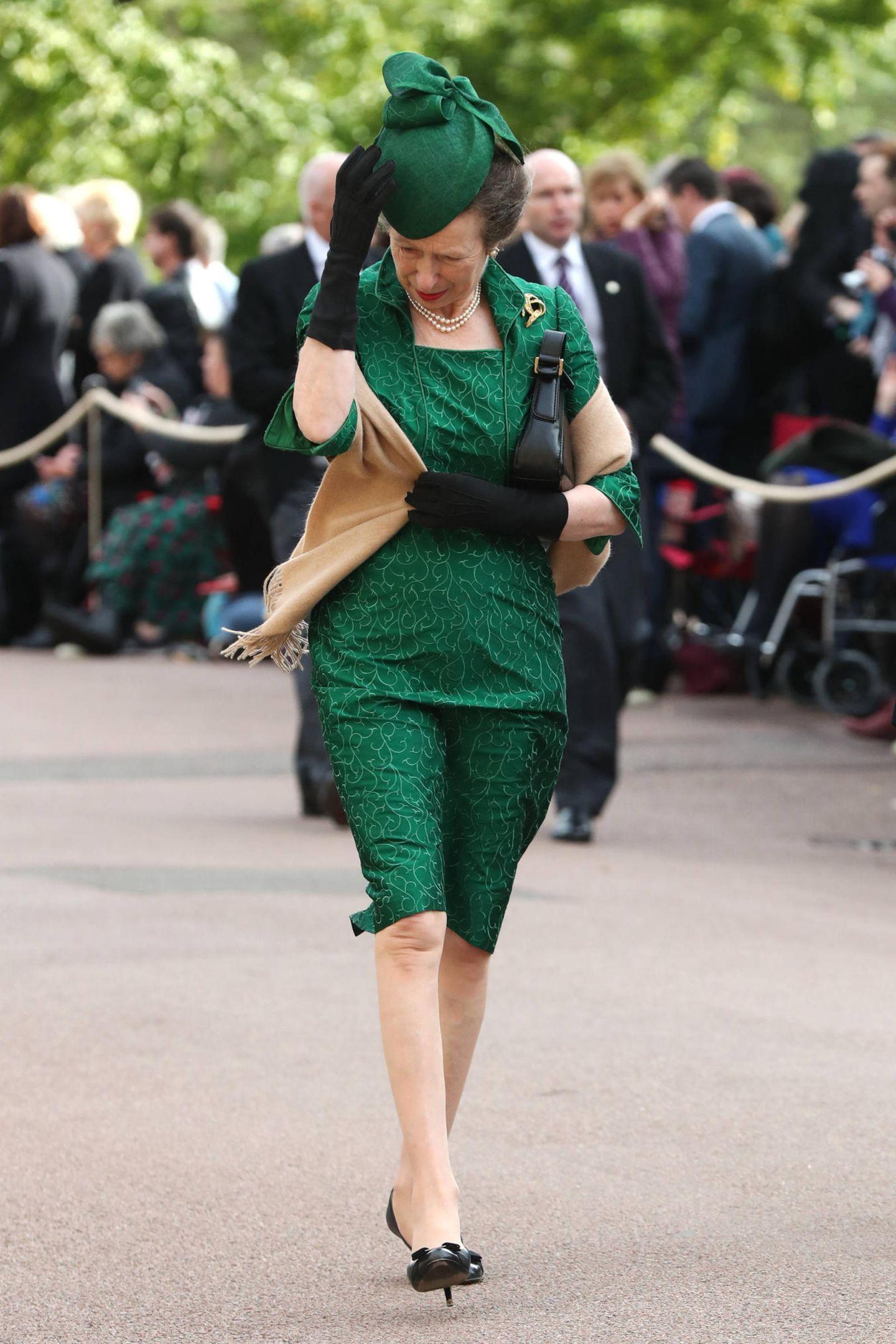 Prinzessin Anne hat bei ihrer Ankunft mit dem Wind zu kämpfen. Ihren Hut, der perfekt zu ihrem ganzen Look passt, hält sie dennoch erfolgreich auf dem Kopf.