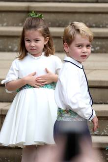 Prinzessin Charlotte und Prinz George stehlen mal wieder allen die Show. Als Blumenkinder kommen sie kurz vor der Braut an der Kirche an. Prinz George trägt eine lange, dunkelblaue Hose, ein weißes Hemd und einen grün-gemusterten Kummerbund.