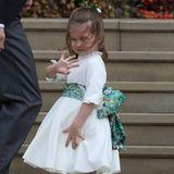 """Prinzessin Charlotte winkt den Fotografen und wartenden Zuschauern. Auch sie trägt eine breite grün-gemusterte Schleife und ein weißes Kleid. Alle Looks der Blumenkinder stammen vom Londoner Label """"Amaia Kids"""". Es ist das gleiche Label, das auch Sophie Carter für ihre Blumenkinder wählte."""