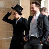 Topmodel Cara Delevingne sorgt mit ihrem Outift für Aufsehen: Statt in einem Kleid erscheint das Model in einem eleganten, schwarzen Anzug inklusive Hut. Doch der sitzt nicht immer perfekt.