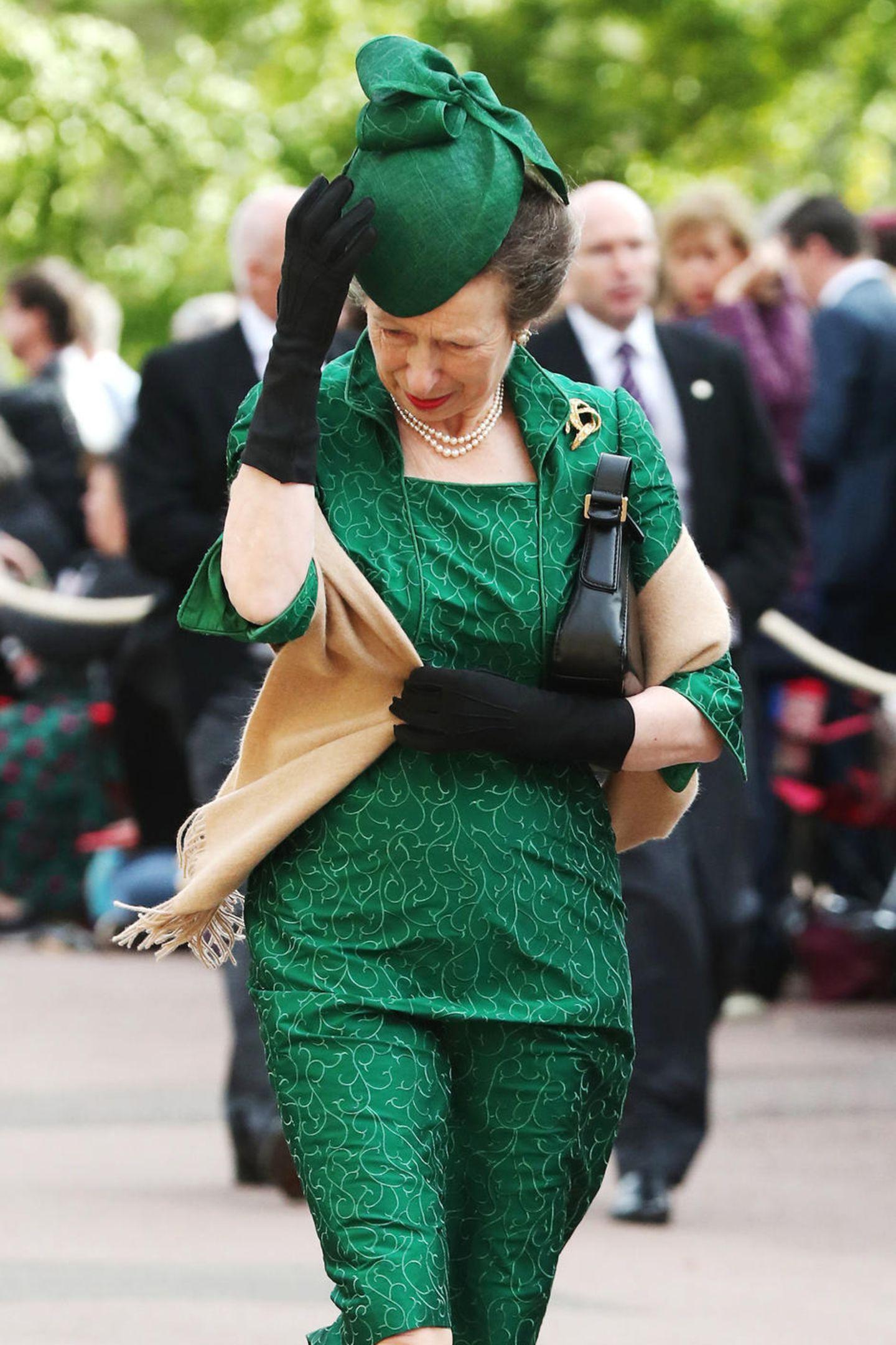Wie so viele Gäste, hat auch Prinzessin Anne Mühe ihren Hut bei dem starken Wind festzuhalten.