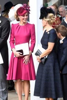 Zu ihrem leuchtenden Dress von Alexander McQueen kombiniert die schöne Ehefrau von Prinz William einen farblich abgestimmten Fascinator und eine bordeauxfarbene Clutch, sowie passende High Heels.