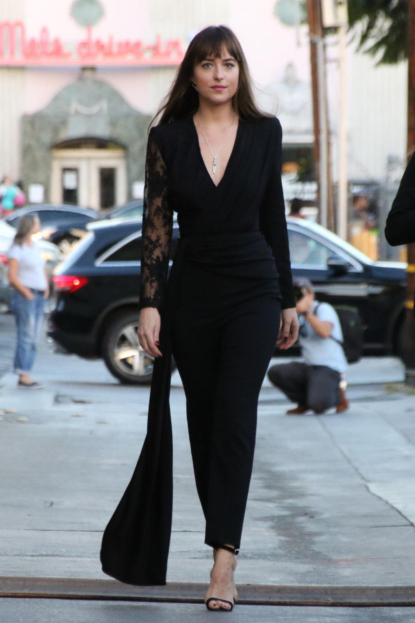 Schauspielerin Dakota Johnson erscheint in einem schwarzen Overall mit Spitzeneinsatz am rechten Arm, tiefen V-Ausschnitt und einem sogenanntenFishtail,einer angeschnittenen Schleppe, zur Jimmy Kimmel Live Show in Los Angeles. Der eng-geschnittene Overall von Dakota sieht nicht nur wahnsinnig sexy aus, räumt sie damit auch die kürzlich kursierenden Schwangerschaftsgerüchte auf. Denn Platz für ein potenzielles Schwangerschaftsbäuchlein gibt es bei diesem Look nicht.