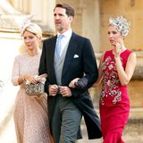 Stylisches Trio:Prinzessin Marie-Chantal von Griechenland, Prinz Pavlos von Griechenland und Prinzessin Olympia von Griechenland zeigen wie perfekte Wedding-Looks auszusehen haben. Marie-Chantal setzt auf ein rosafarbenes Midi-Spitzenkleid, Olympia glänzt in einem roten Kleid mit aufwändigen Stickereien.