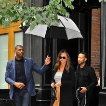 Bei Regenwetter den Schirm selber tragen? Nichts für Chrissy Teigen! Die lässt ihn sich von ihrem Bodyguard halten.