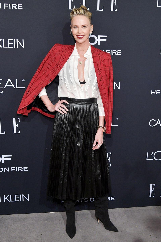 Charlie Theron setzt mit ihrem rotkarierten Dior-Blazer einen schönen Kontrast zum übrigen Schwarz-weiß-Style.