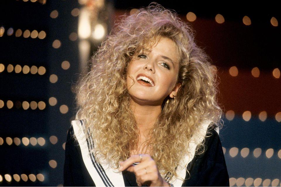 """Eine riesige Lockenmähne, dezentes Make-up und ein niedliches Outfit mit Kragen:Die 23-Jährige stand damals noch als Sängerin auf der Bühne. Heute ist sie als Moderatorin des Formats""""Bauer sucht Frau"""" ein absoluter TV-Liebling."""