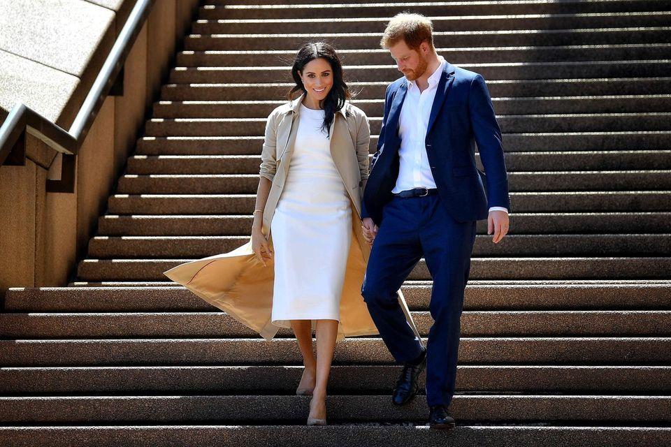 Eine Aufnahme von Herzogin Meghan und Prinz Harry auf Australienreise - sie laufen eine Treppe hinunter und Meghans Mantel weht