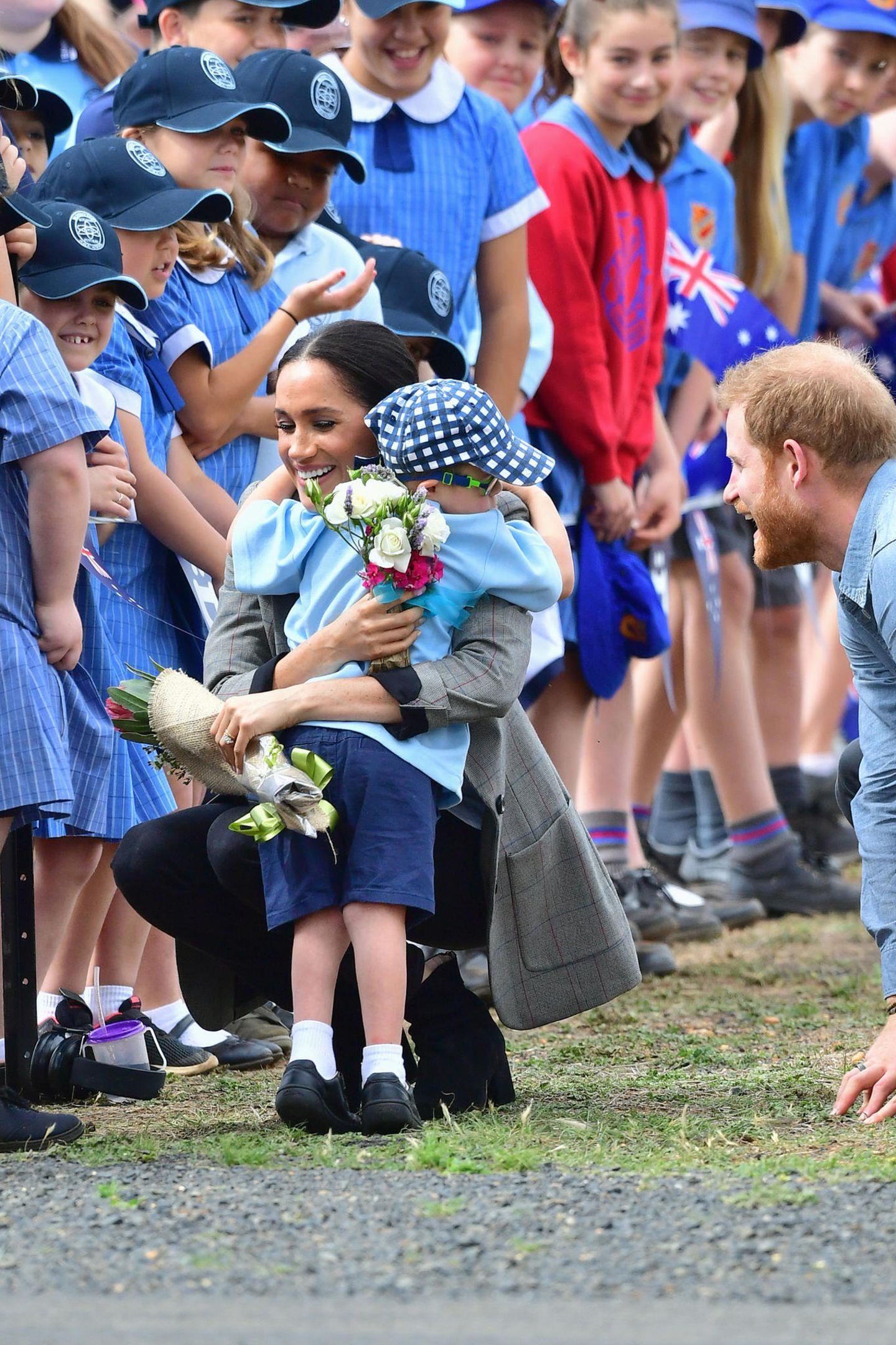 Tag 2  Auch Herzogin Meghan wird von dem kleinen, royalen Fan fest umarmt.