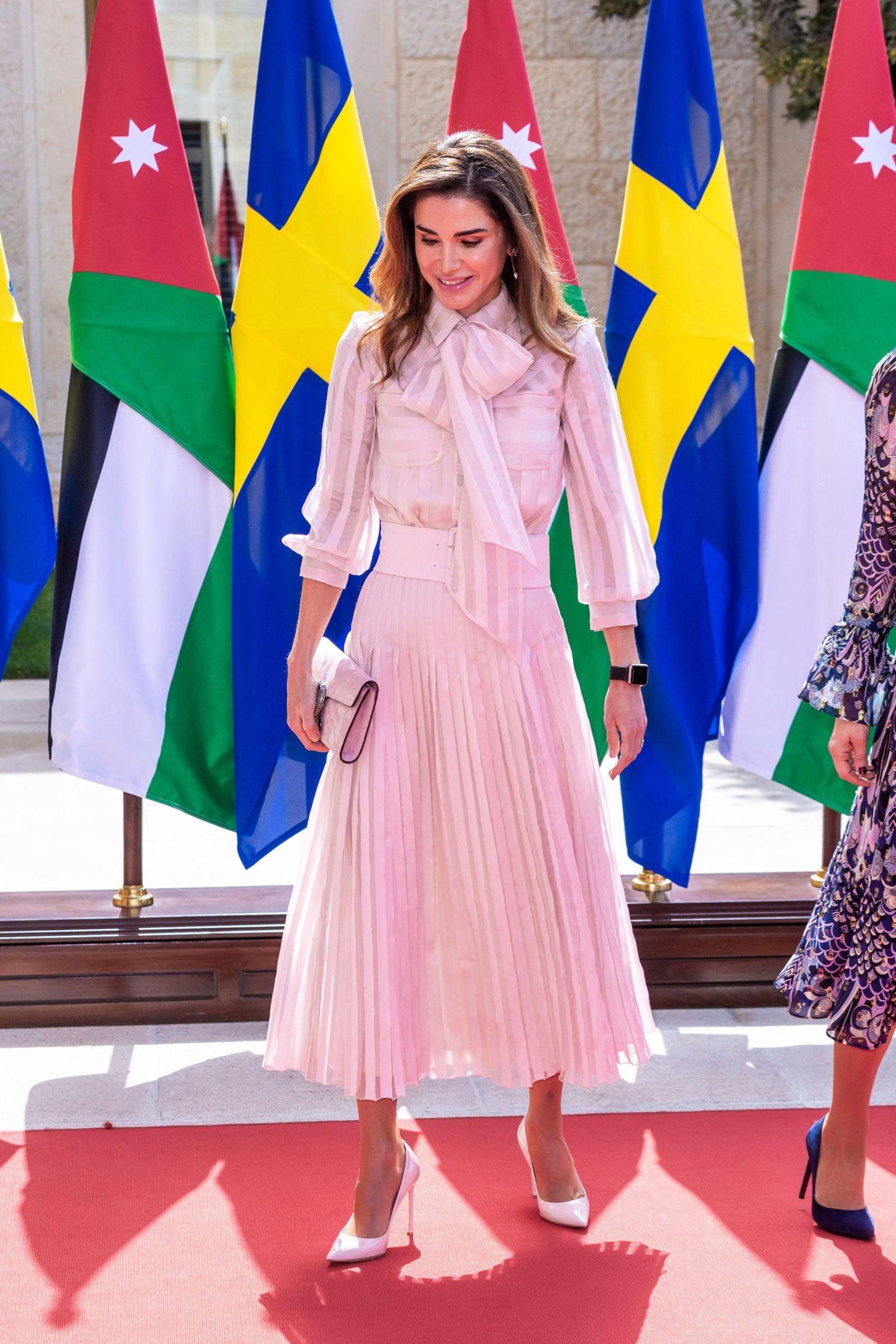 Königin Rania setzt auf einen einfarbigen, mädchenhaften Look. Sie trägt ein rosafarbenes Outfit des Luxus-Labels Ralph & Russo. Dazu kombiniert sie Accessoires in hellen Farbtönen.