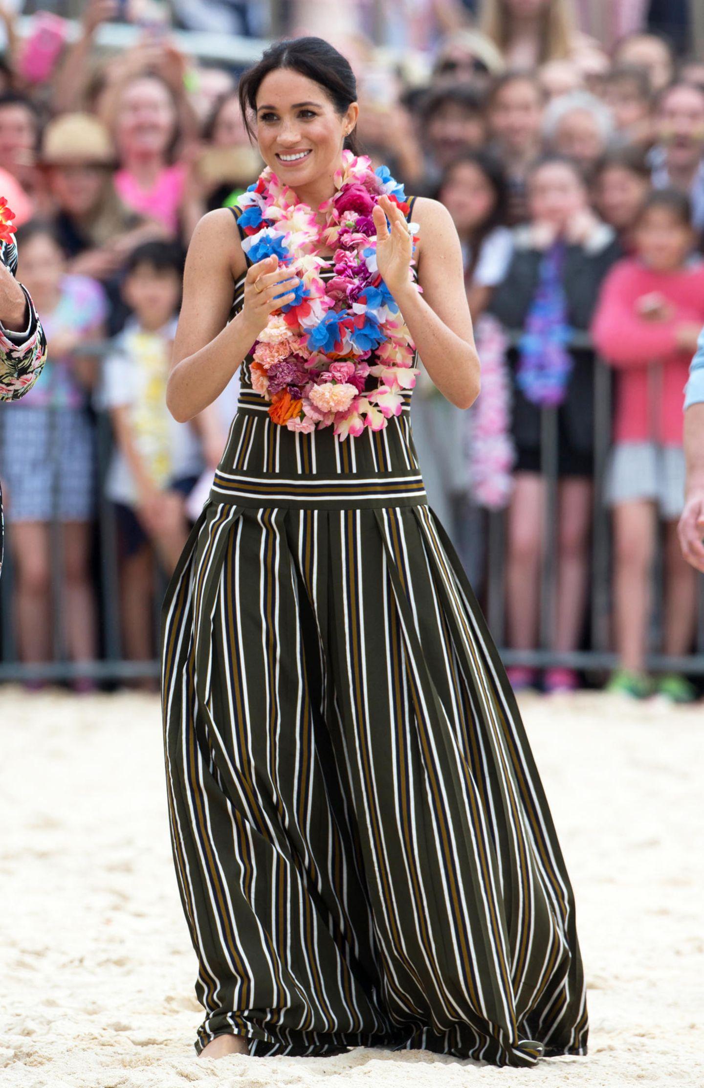 Aloha Meghan! Beim Besuch des Bondi Beach zeigt sich Herzogin Meghan von einer ganz anderen Seite. Im gestreiften Kleid von Martin Grant sieht man sieerstmals in einem Maxikleid und natürlich wählt Meghan eineLuxus-Variante für 1.222 Euro. Ihr wohl schönsten Accessoire - neben der Blumenkette - ihr strahlendes Lächeln. Doch ihre Schuhwahl würde der Queen so gar nicht gefallen ...