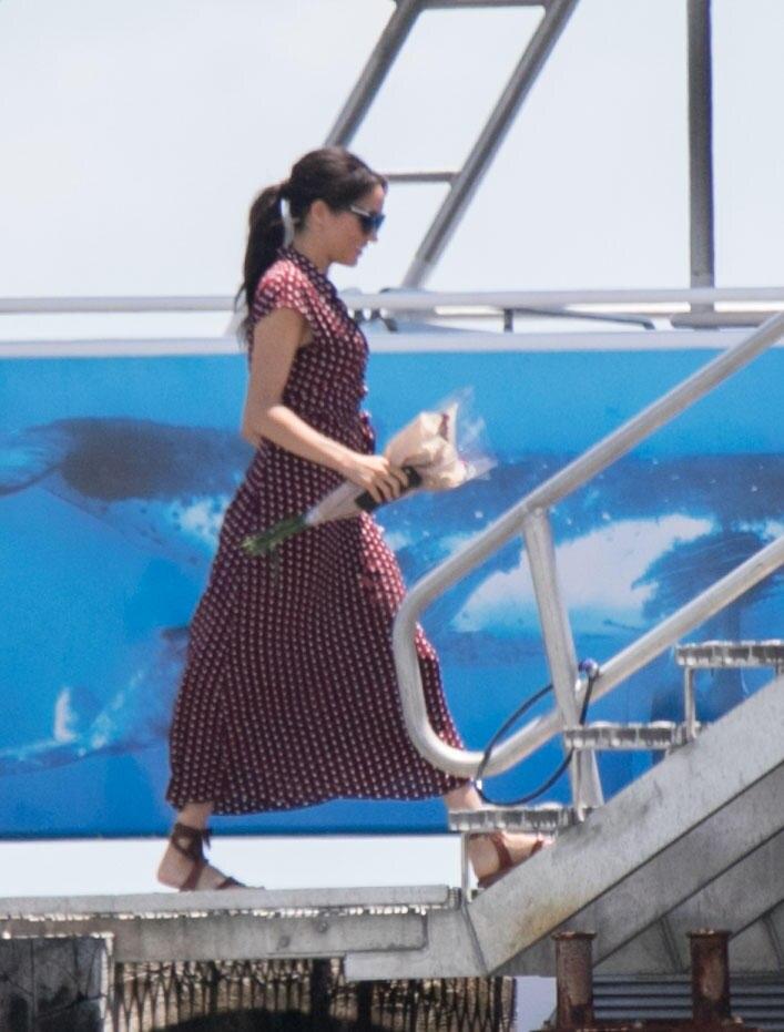 """Während der Australien-Reise zusammen mit Prinz Harryzeigt sich Herzogin Meghan in einem dunkelroten Midi-Kleid des bekannten Modelabels """"& Other Stories"""", und das war ein echtes Schnäppchen:Das Kleid mit kurzen Ärmeln und einem hübschenPolka-Dot-Musterkostet gerade einmal 99 Euro. Dazu kombiniertMeghan flache Römersandalen aus Lederund eine dunkle Sonnenbrille. Doch auch ihre Schwägerin Herzogin Catherine scheint diesen lässigen Schwangerschaftslook zu lieben undgriff im letzten Jahrzu einem ähnlichen Kleid ..."""