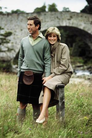 Prinzessin Diana sitzt neben dem stehenden Prinz Charles.