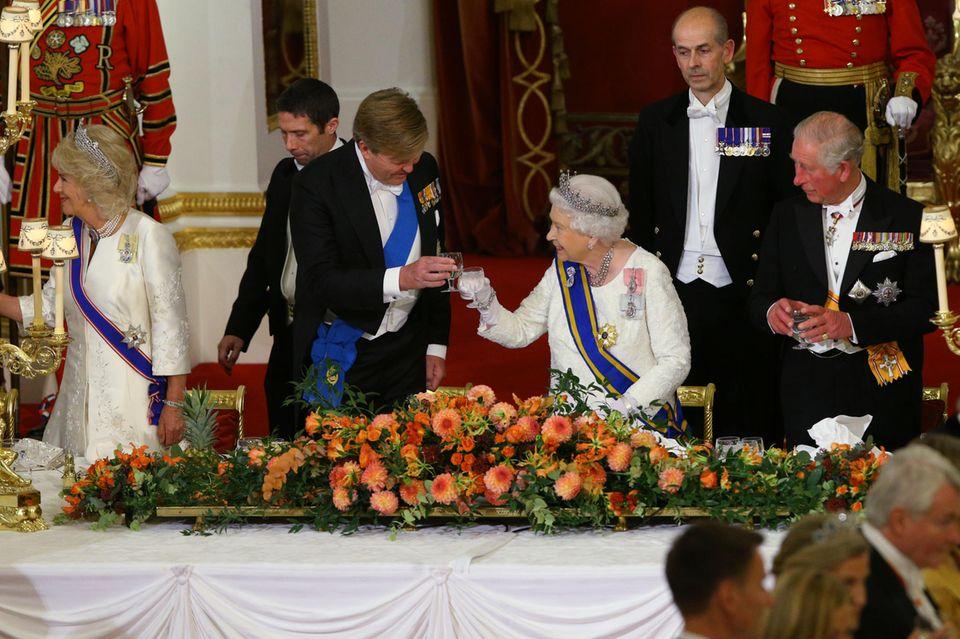 """Beim jüngsten Auftritt von Queen Elizabeth handelte es sich ebenfalls um ein Staatsbankett, also um ein """"White Tie-Dinner"""". Zu erkennen ist das nicht nur an den Diademen, die die Queen und Herzogin Camilla tragen, sondern auch an König Willem-Alexander und Prinz Charles. Beide erschienen im schwarzen Frack und weißer Fliege."""