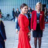 Zur SicherheitsmesseSKYDD 2018 in Stockholm erscheint Prinzessin Victoria in einem wunderschönen Midi-Kleid mit fließender Struktur und kleinem Taillen-Gürtel in Knallrot. Passend dazu wählt sie farblich abgestimmte Pumps und eine Clutch - ebenfalls in Rot.