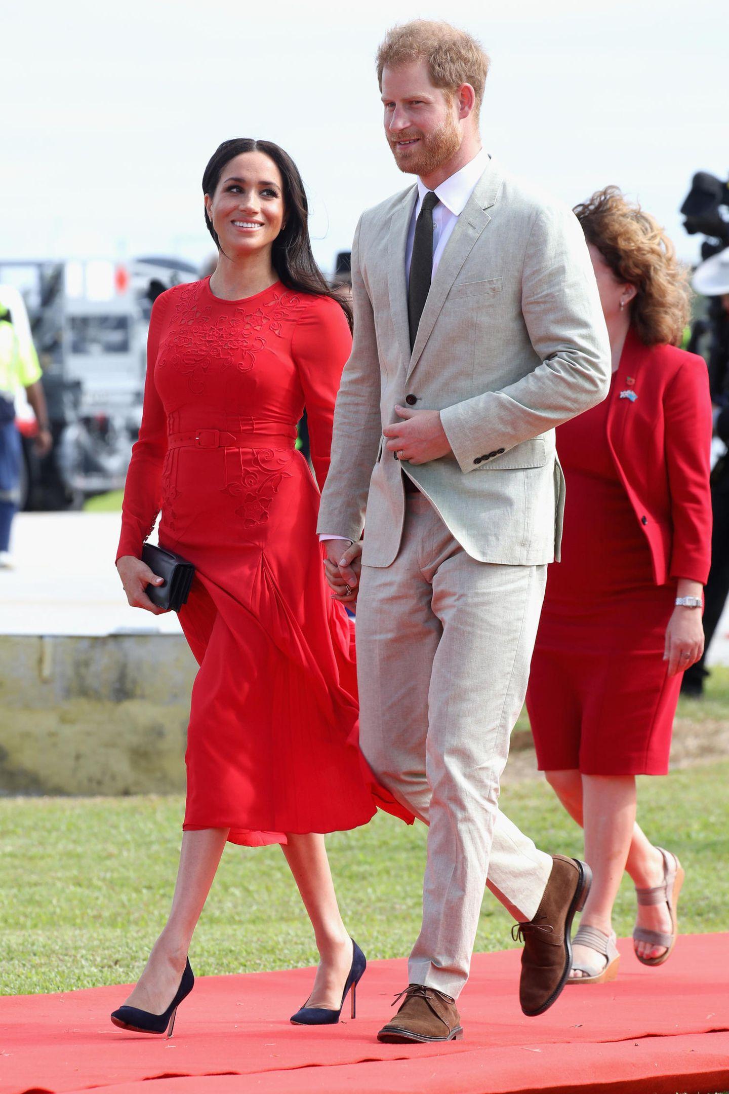 Tag 10  Angekommen auf der südpazifischen Insel Tonga legt das Pärchen einen strahlenden Auftritt am Flughafen hin. Herzogin Meghan wirft ihrem Harry verliebte Blicke zu.