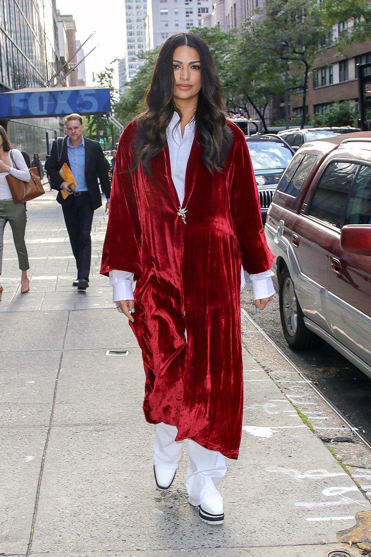 """Ist denn schon Weihnachten? Wenn man Camila Alves so betrachtet, könnte es schon fast so weit sein. Paparazzi lichten die Frau von Matthew McConaughey im Oktober 2018 in den Straßen von New York ab. Vor der herbstlichen Oktober-Kälteschützt sie sich mit einem roten Samt-Umhang des Labels """"Alica + Olivia"""". Dazu kombiniert sie eine 70er-Jahre-Schlaghose, Bluse und Stella-McCartney-Schuhe in Weiß."""
