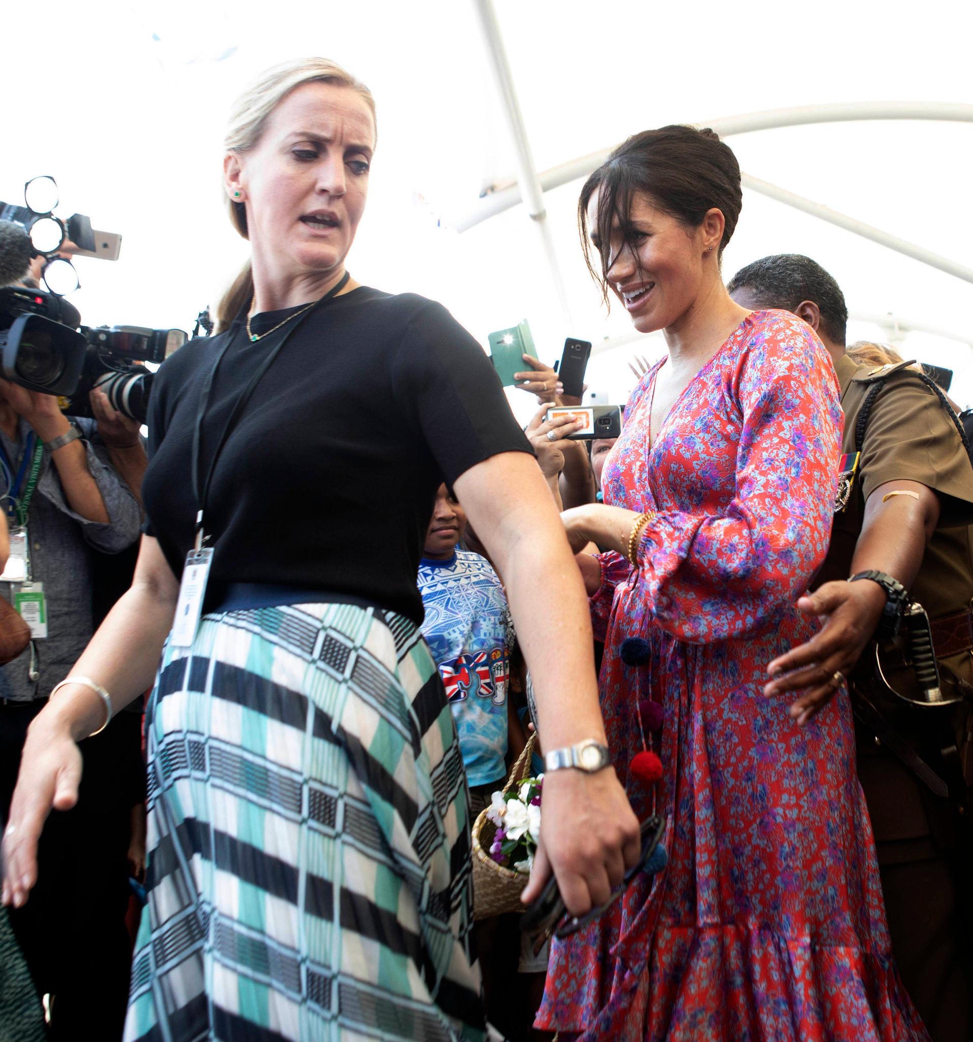 Herzogin Meghan wird von ihrer neuen Personenschützerin aus dem Gedränge eskortiert.