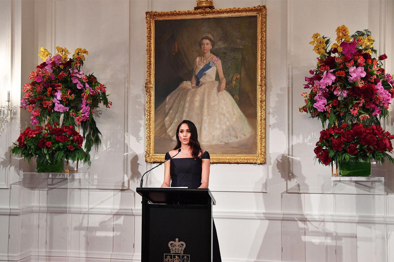 Tag 12  Unter dem Porträt der jungen Queen Elizabeth hält Herzogin Meghan während des Empfangs im Government House ein Rede.