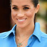 Passend zum hellblauen Kleid hat sich Meghan für ihren Besuch in Tonga eine Halskette mit drei tropfenförmigen, hellblauen Edelsteinen um den royalen Hals gehangen. Die Kette stammt von Pippa Small und kostet ca. 1685 Euro. Die kleinen, aber auch dreiteiligen Diamant-Stecker könnte man dabei fast übersehen.